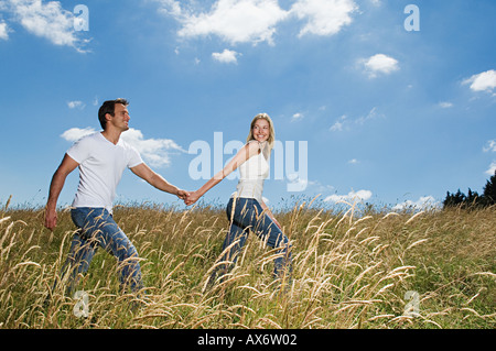 Couple walking in a field - Stock Photo