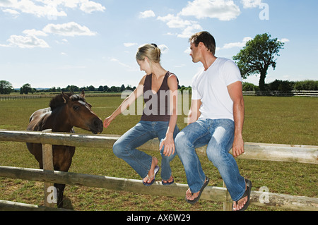 Couple sitting on a fence with horse - Stock Photo