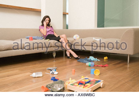 Mother on phone in messy room - Stock Photo
