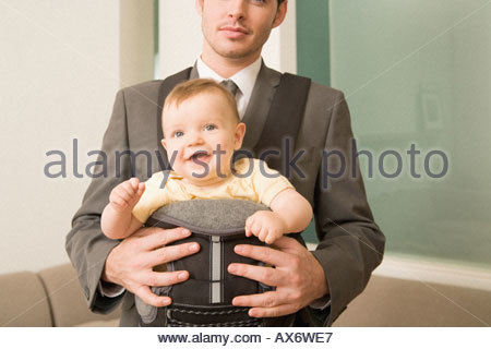 Businessman with his son in a baby carrier - Stock Photo