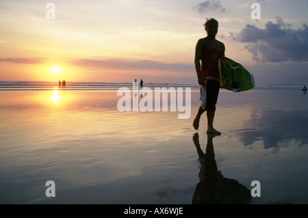 Sunset on Kuta Beach surfers carry their surfboards from the ocean after a long day riding the waves - Stock Photo