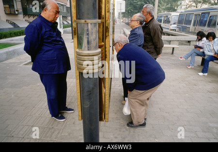 Chinese men in traditional Mao suits with Mandarin collars in Beijing read newspapers posted on a publc board - Stock Photo