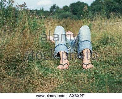 Woman lying in a field - Stock Photo