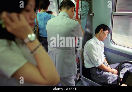 Chinese commuters ride on the KCR train from Hong Kong to China A woman talks on a mobile phone in the foreground - Stock Photo