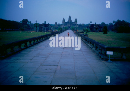 A single person walks down a long pathway to Ankor Wat Temple, Cambodia. - Stock Photo