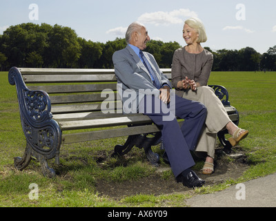 Elderly couple sitting on a park bench - Stock Photo