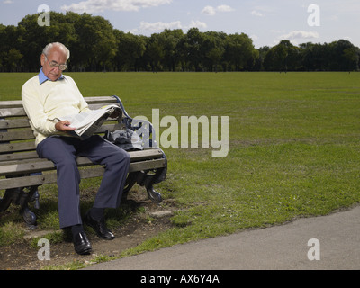 Elderly man reading a newspaper in a park - Stock Photo