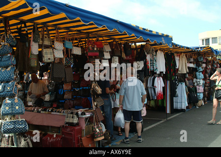 An older european couple look at handbags and leather goods on a tourist market stall in Gran Canaria - Stock Photo