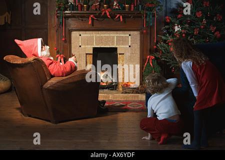 Children watching santa claus in living room - Stock Photo