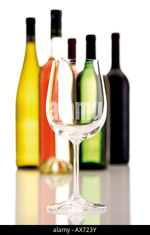 Wine glass in front of wine bottles, close-up - Stock Photo