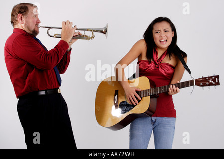 Stock Photograph of a man playing a trumpet into the ear of a teen girl with a guitar - Stock Photo