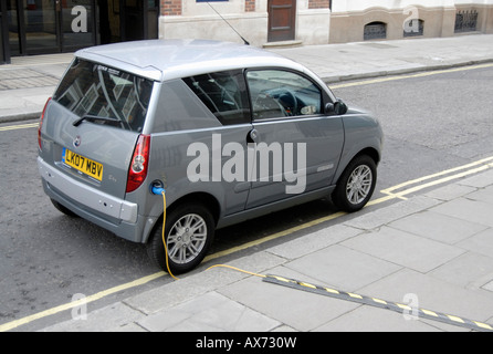 Electric car plugged into extension cord for recharging on street, City of Westminster, London SW1, Engand - Stock Photo