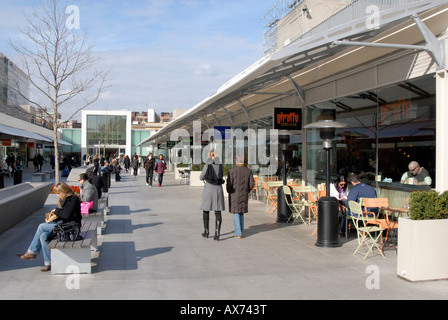 Open public piazza with people enjoying lunch hour amidst shops and restaurants of Brunswick Centre, Bloomsbury, - Stock Photo