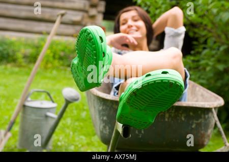 Young woman relaxing in wheelbarrow, portrait - Stock Photo