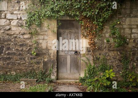 walled garden wooden doorway with ivy surrounding Oxford - Stock Photo