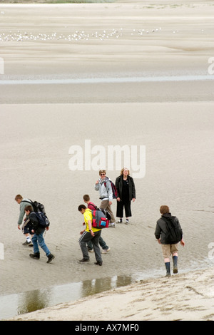 Party of students starting out on field trip across mud flats of Somme estuary Saint Valery sur Somme - Stock Photo