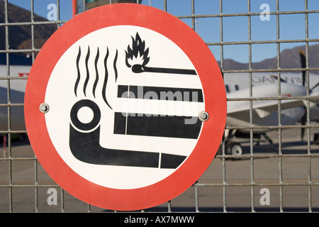 no smoking sign on airport fence - Stock Photo