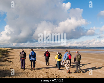GROUP of YNYS MON RAMBLERS walking on the sandy beach in Red Wharf Bay Llanddona Isle of Anglesey North Wales UK - Stock Photo