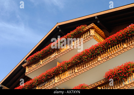 Swiss chalet with geranium flowers on the balcony Crans Montana Valais Switzerland - Stock Photo