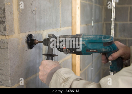 a building drilling large 3 inch (76mm) holes in a wall using an SDS attachment to allow fitting of metal wall boxes - Stock Photo
