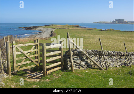 Stile and wall at Cemlyn Bay with Wylfa nuclear power station in the background Anglesey North Wales UK - Stock Photo
