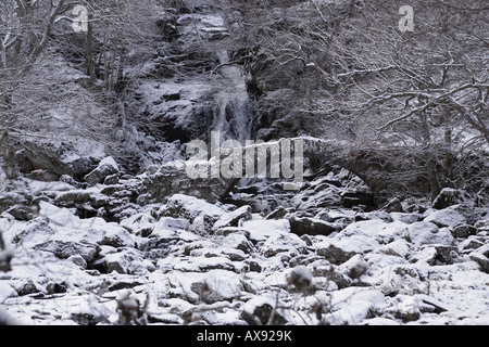 Old packhorse bridge and waterfall in snow Glen Lyon Scotland UK - Stock Photo