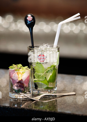 Mojito cocktail caipirinha mint julep drink in Havana Club glass with appetizer and fork - Stock Photo