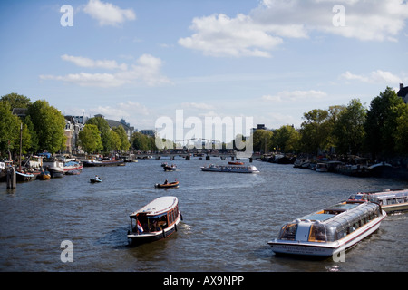 boats on a river and trees in the right and left part witch blue sky and some clouds - Stock Photo