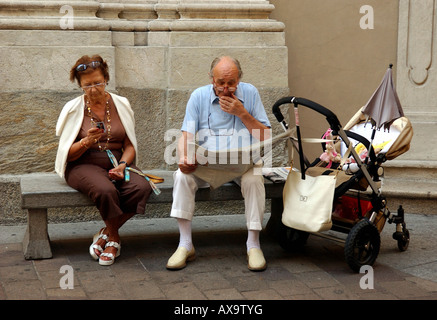 Grandparents sitting on a bench with their grandchild sleeping in a pram, Switzerland - Stock Photo