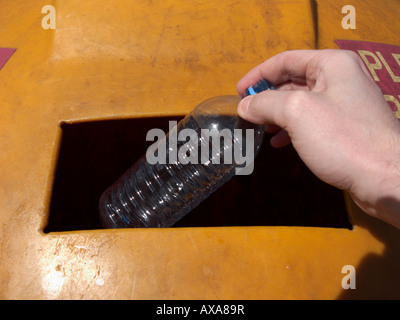 mans hand placing a recyclable empty clean plastic bottle in a recycling bin at recycling depot - Stock Photo