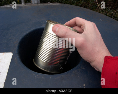 mans hand placing a recyclable empty large clean metal can in a recycling bin at recycling depot - Stock Photo