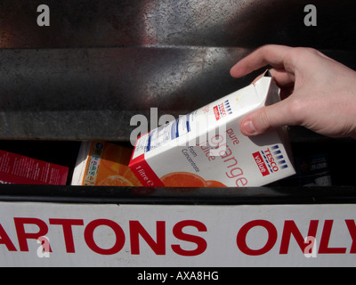 mans hand placing a recyclable empty cleaned fruit juice container in a recycling bin at recycling depot - Stock Photo