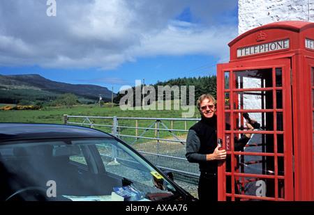 man at Rural Telephone Box and Royal Mail Box Isle of Mull Scotland - Stock Photo