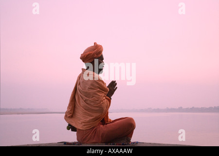 Holy man meditate on the river bank of the Ganges Varanasi India - Stock Photo