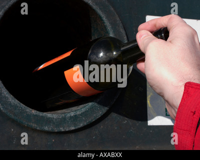 mans hand placing a empty green wine bottle in a recycling bottle bank bin at recycling depot - Stock Photo