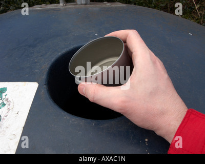 mans hand placing a recyclable empty small clean metal can in a recycling bin at recycling depot - Stock Photo