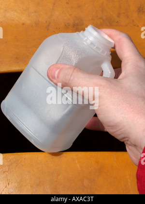 mans hand placing a recyclable empty opaque pint milk plastic bottle in a recycling bin at recycling depot - Stock Photo