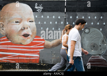 Young couple walking in front a graffiti, Seville, Spain - Stock Photo
