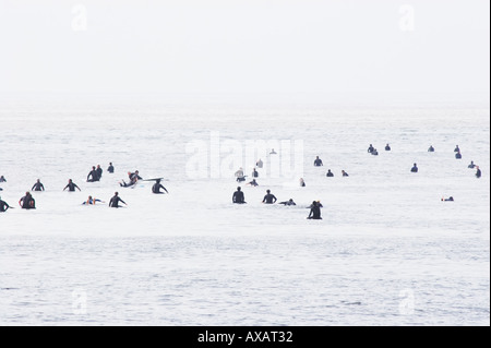 Surfers at Malibu beach waiting to catch a wave on a cold foggy morning. - Stock Photo