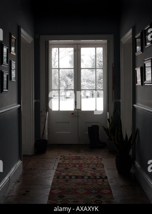 View down Georgian hallway to reveal it is snowing hard outside - Stock Photo