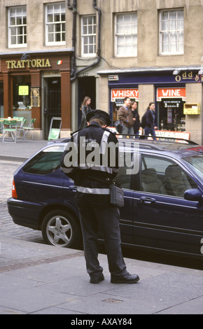 Parking attendant writing a ticket for an illegally parked car on the Royal Mile, Edinburgh - Stock Photo