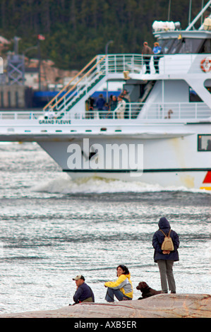 People watching, from shore, a 'Croisières AML' whale watching cruising ship passing by on the Saguenay river - Stock Photo