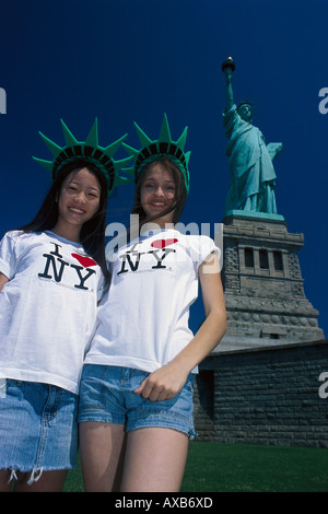 Two smiling girls in front of the Statue of Liberty, Liberty Island, New York USA, America - Stock Photo