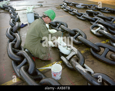 Worker painting the anchor chain white, dry dock, Queen Mary 2, Saint-Nazaire, France - Stock Photo