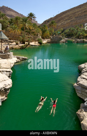Two girls swimming in the turquoise pools of Wadi Bani Khalid in the eastern Hajar mountains of the sultanate of - Stock Photo