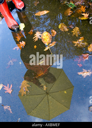 MR autumn weather reflection of a person with umbrella in rubber boots in a puddle - Stock Photo