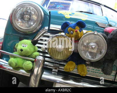 front detail of blue Mini with cuddly toys behind front bumper - Stock Photo