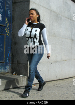 young woman wears t-shirt with writing 'Bronx' and is speaking on her cell phone, USA, Bronx, New York - Stock Photo