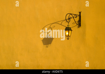 Horizontal close up of old fashioned street lamp casting long shadows on a wall in the evening sunshine. - Stock Photo