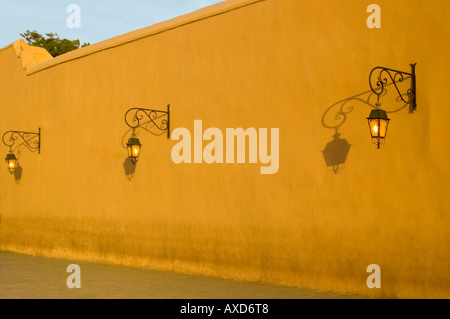 Horizontal view of three old fashioned street lamps in a row casting long shadows on a wall in the evening sunshine. - Stock Photo